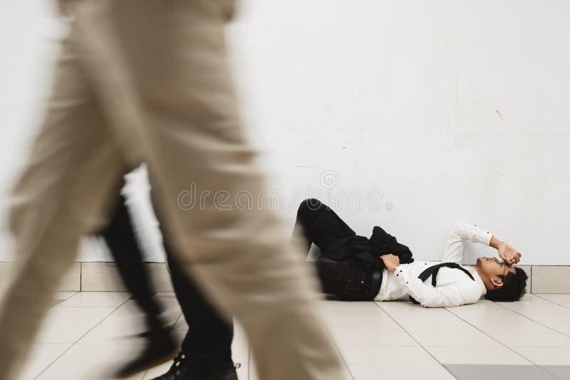 Молодой азиатский бизнесмен лежа вниз на дорожке думая об его проблемы и посмотреть настолько подавленный стоковое фото