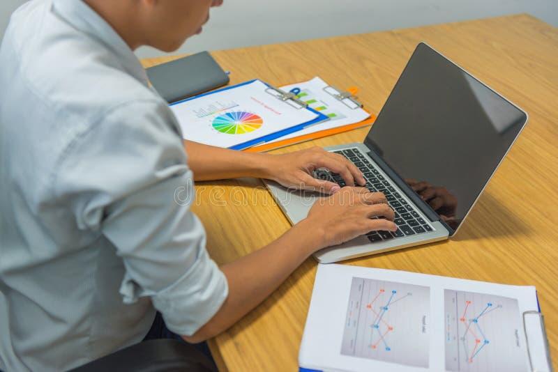 Молодой азиатский бизнесмен работая на ноутбуке в офисе стоковые изображения