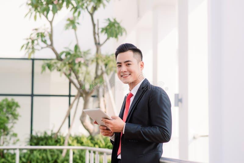 Молодой азиатский бизнесмен работая на планшете, образе жизни современного мужчины технология для того чтобы связывать, сообщения стоковое изображение rf
