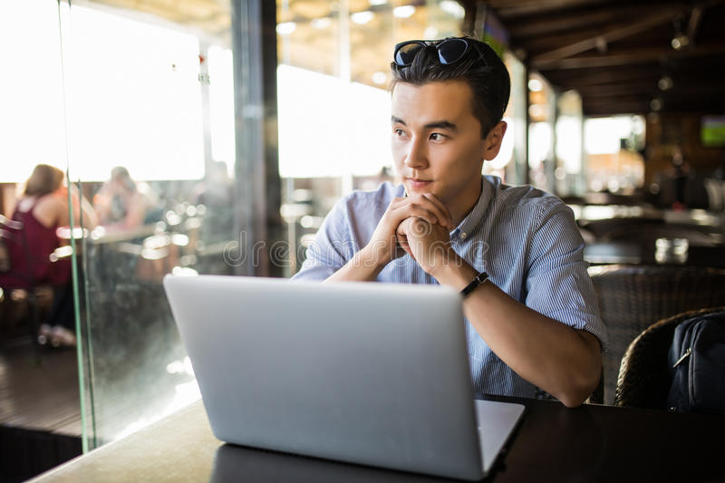 Молодой азиатский бизнесмен работая с портативным компьютером и тетрадью в предпринимателе кафа вскользь Работать работа стоковое изображение