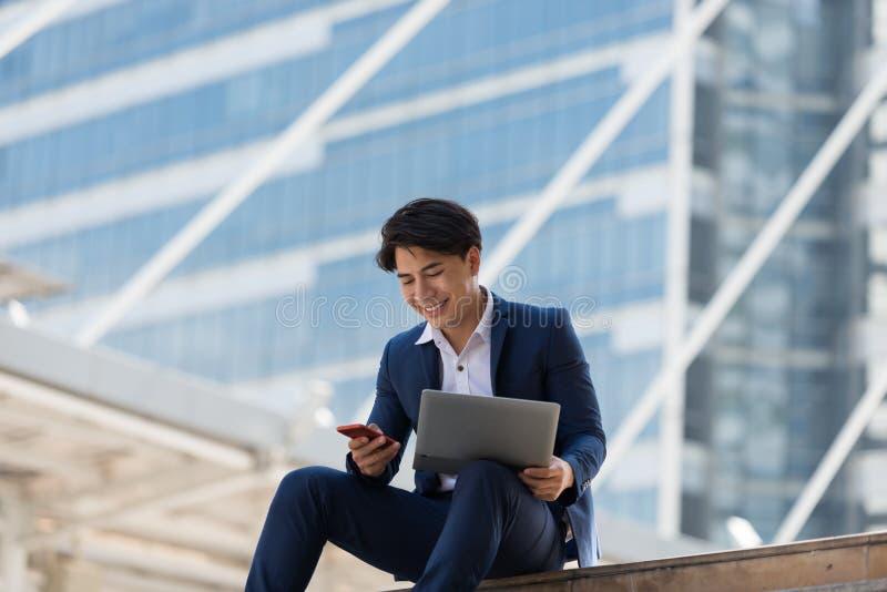 Молодой азиатский бизнесмен счастливый Он смотря на мобильном телефоне и wo стоковая фотография