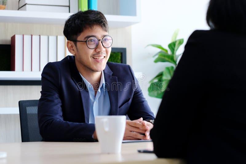Молодой азиатский бизнесмен усмехаясь на деловой встрече, собеседовании для приема на работу, в офисе, бизнесмены, концепция обра стоковое фото rf