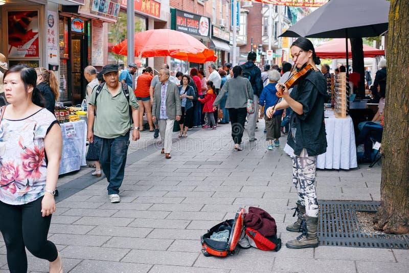 Молодой азиатский женский музыкант улицы играя скрипку и пробуя собрать деньги от людей проходя мимо в Чайна-таун, Монреаль, стоковая фотография