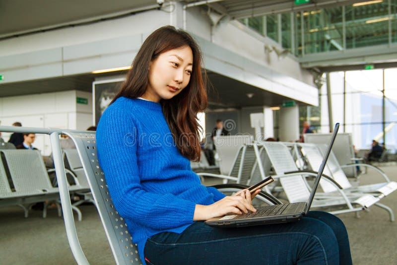 Молодой азиатский женский пассажир используя ноутбук и умный телефон пока сидящ на месте в терминальной зале и ждущ полет в аэроп стоковые изображения rf