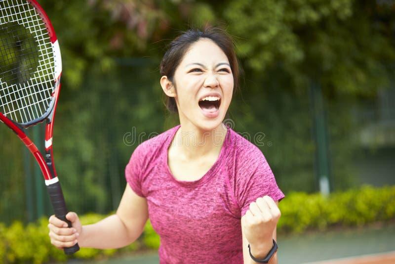 Молодой азиатский женский теннисист празднуя после вести счет стоковая фотография