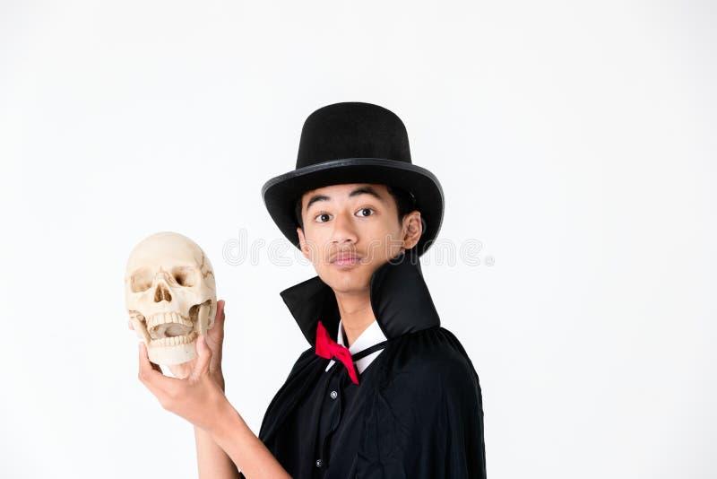 Молодой азиатский мальчик в черной крышке и черной шляпе держа и смотря стоковые фото