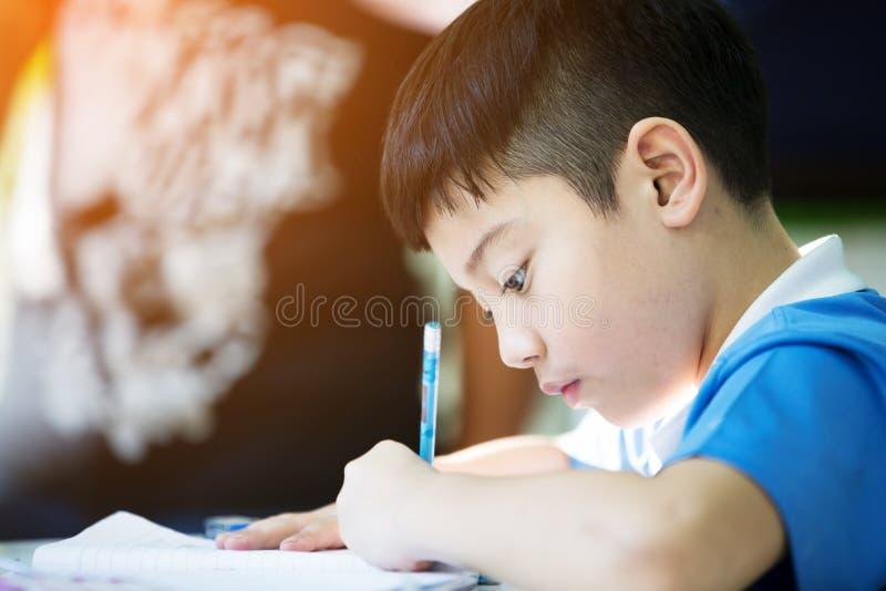Молодой азиатский мальчик делая его домашнюю работу стоковые фото