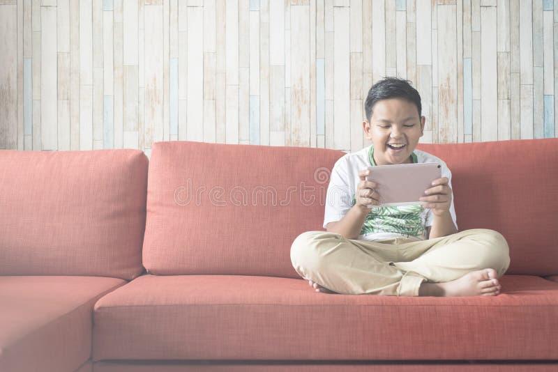 Молодой азиатский мальчик используя цифровую таблетку на софе дома сидя положив ногу на ногу стоковое фото