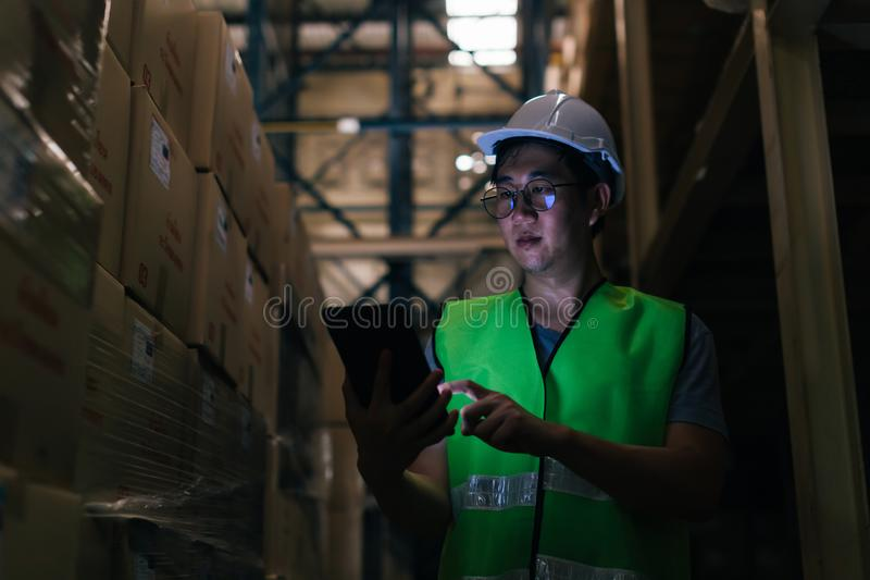 Молодой азиатский мужской работник склада используя цифровой планшет внутри склада стоковая фотография
