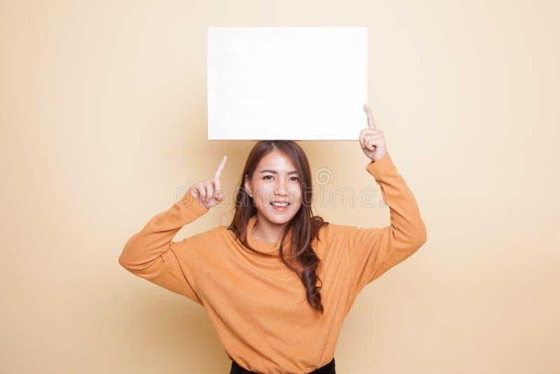 Молодой азиатский пункт женщины для того чтобы прикрыть знак стоковая фотография