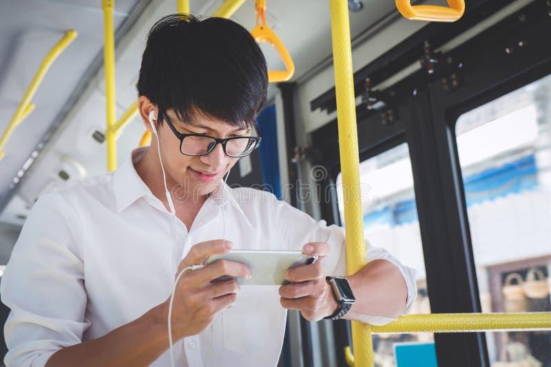 Молодой азиатский путешественник человека стоя на шине используя watc smartphone стоковое фото