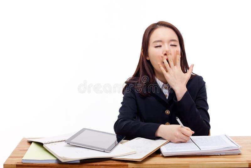 Молодой азиатский студент зевая. стоковое изображение rf