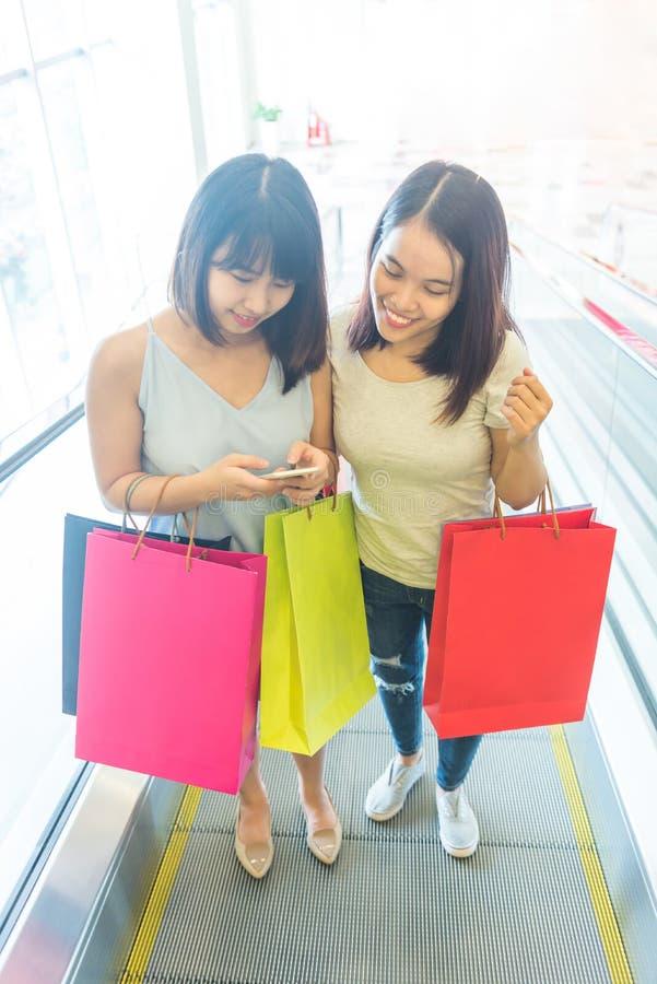 Молодой азиатский ходить по магазинам девушек счастливо идя стоковое изображение