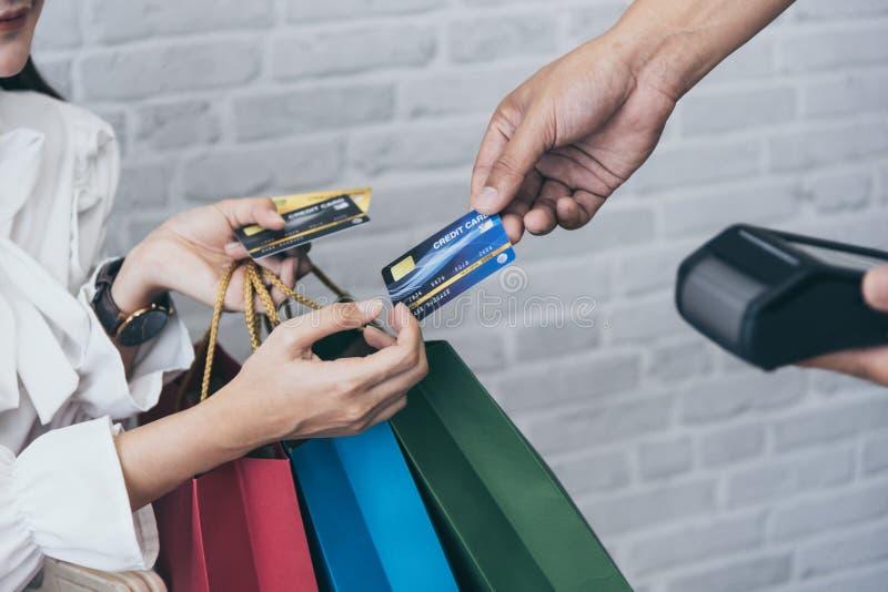 Молодой азиатский ходить по магазинам женщины онлайн с читателем wifi кредитной карточки и машины NFC стоковые фотографии rf