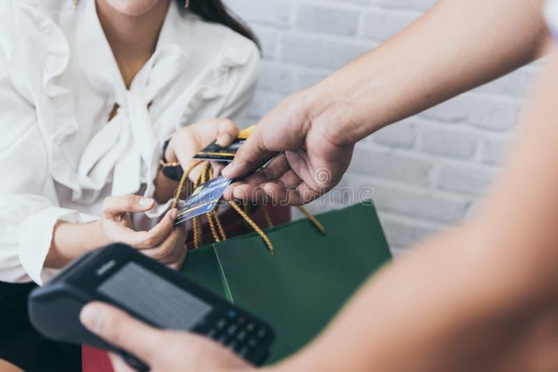Молодой азиатский ходить по магазинам женщины онлайн с читателем wifi кредитной карточки и машины NFC стоковые изображения