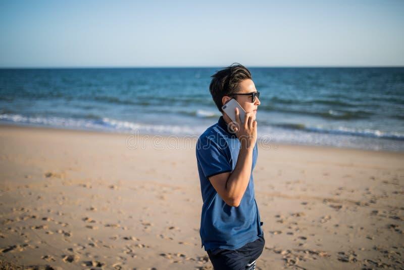 Молодой азиатский человек говоря на телефоне и видит заход солнца на тропическом пляже Турист стоковое изображение rf