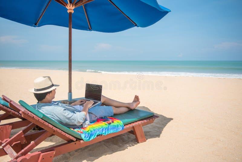 Молодой азиатский человек используя компьтер-книжку на стенде пляжа стоковая фотография rf
