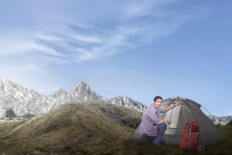 Молодой азиатский человек настроил шатер стоковые фотографии rf
