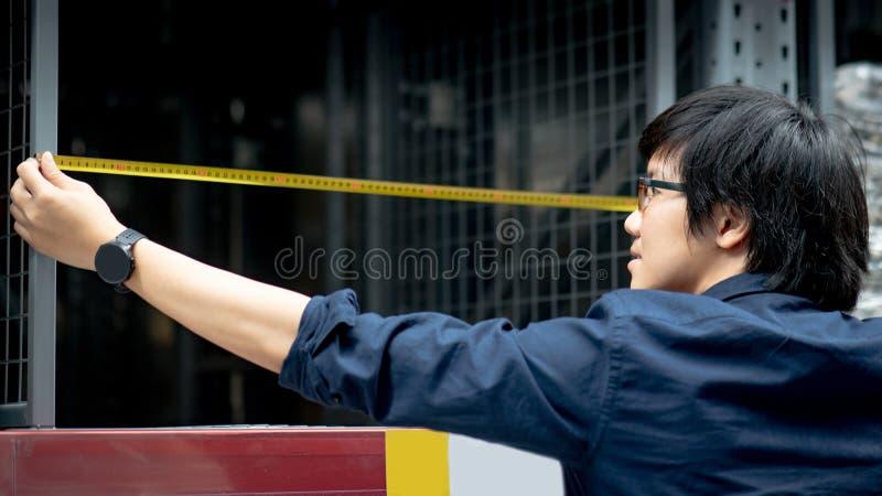 Молодой азиатский человек работника используя рулетку для измеряя полки стоковое фото
