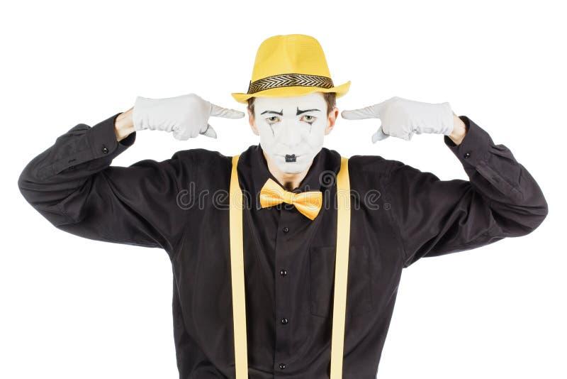 Молодой актер, пантомима, закрывает его руки за его ушами, он стоковая фотография rf