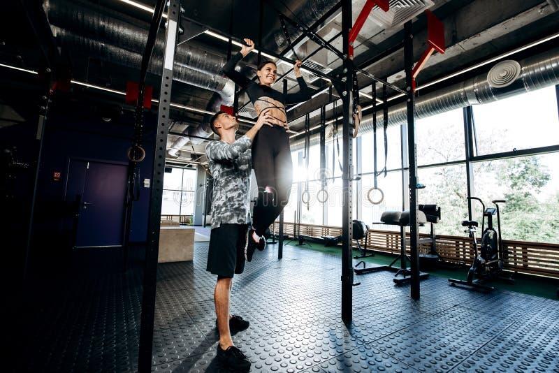 Молодой атлетический человек помогает худенькой милой девушке сделать тягу вверх на баре в спортзале стоковая фотография rf