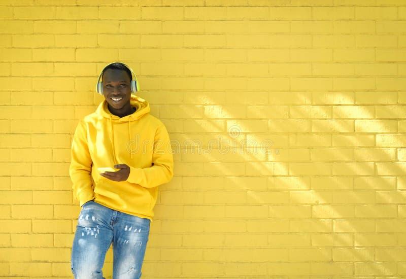 Молодой африканец слушает музыку, опирающуюся на жёлтую стену стоковая фотография rf
