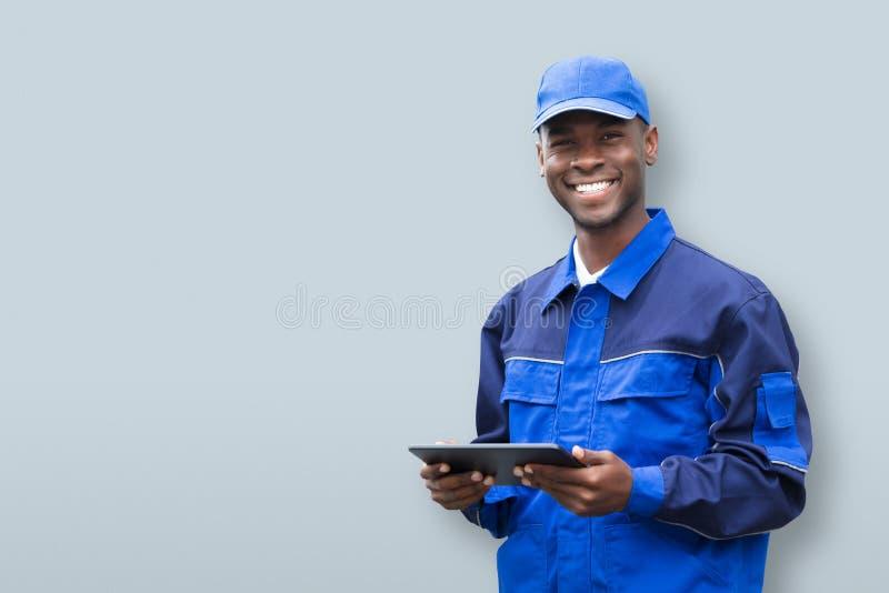 Молодой африканский мобильный телефон удерживания электрика стоковая фотография rf