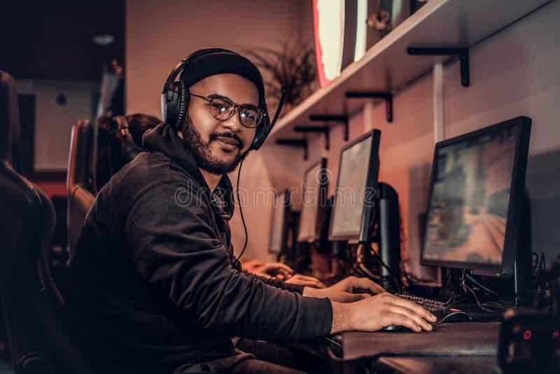Молодой Афро-американский парень, наслаждаясь тратящ время с его друзьями, играя в предназначенной для многих игроков видеоигре н стоковая фотография rf