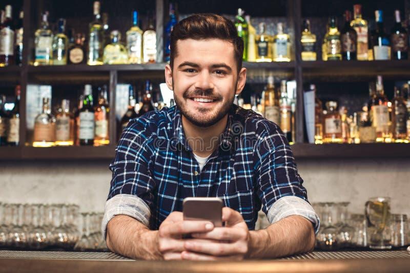 Молодой бармен полагаясь на усмехаться смартфона удерживания счетчика бара жизнерадостный стоковая фотография rf