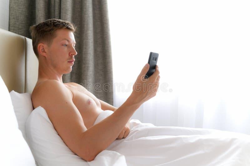 Молодой без рубашки человек используя мобильный телефон в кровати стоковая фотография rf