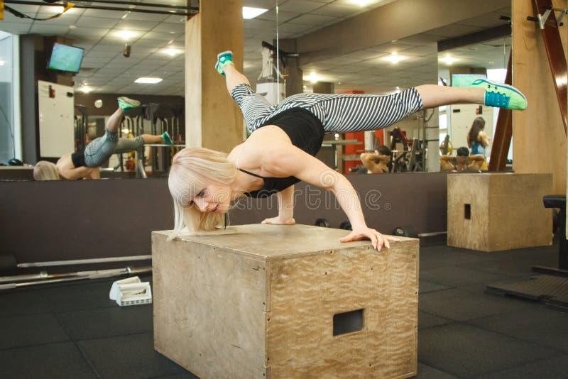 Молодой белокурый женский гимнаст делая handstand в спортзале стоковые фото