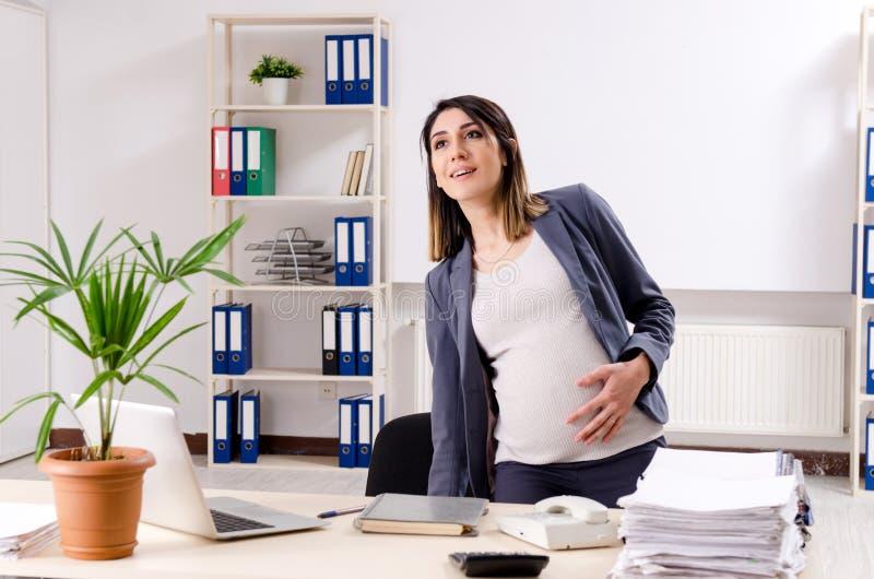 Молодой беременный работник работая в офисе стоковые фотографии rf