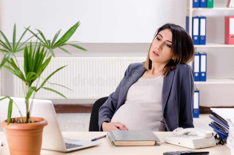 Молодой беременный работник работая в офисе стоковое фото rf
