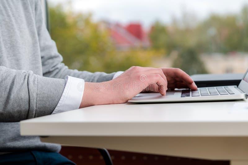 Молодой бизнесмен вручает печатать на клавиатуре компьтер-книжки на офисе стоковая фотография