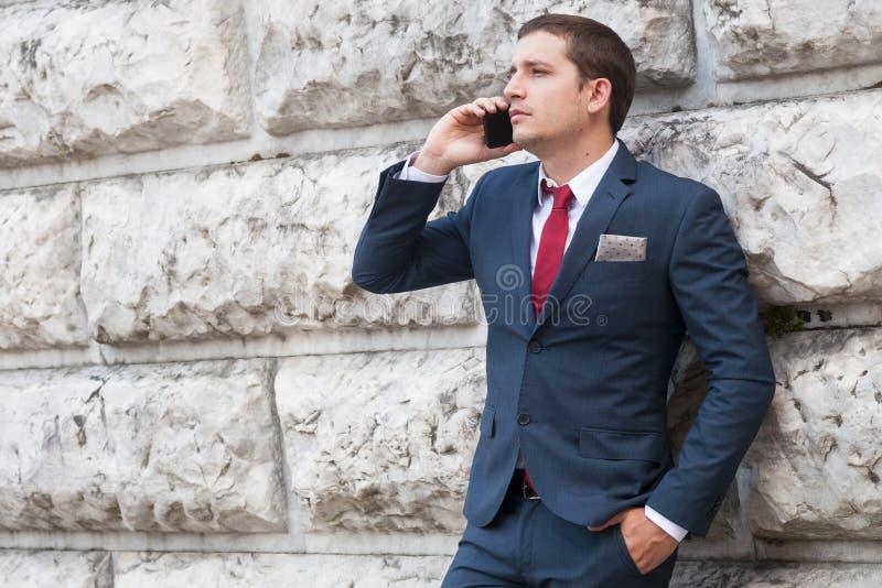Молодой бизнесмен в костюме и связи говоря на smartphone ag стоковое изображение