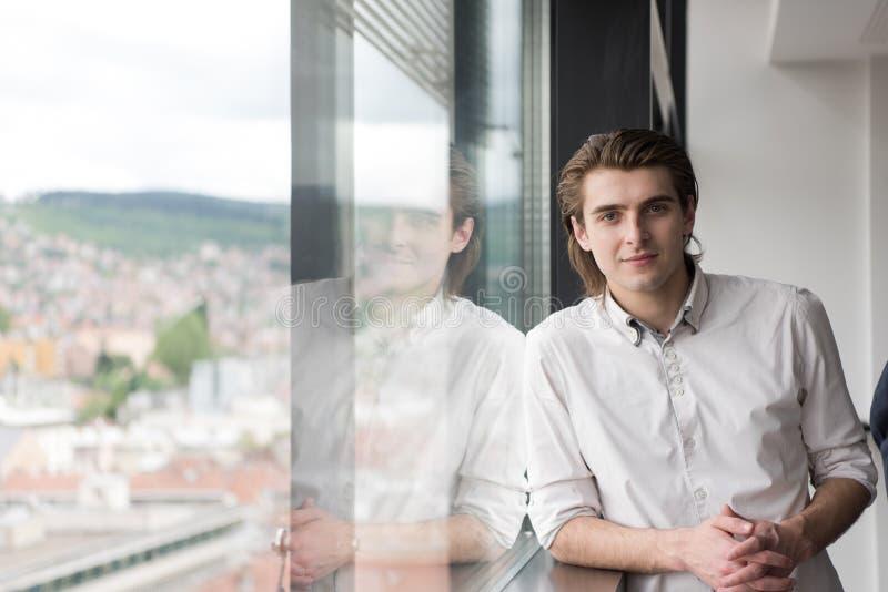 молодой бизнесмен в startup офисе окном стоковая фотография
