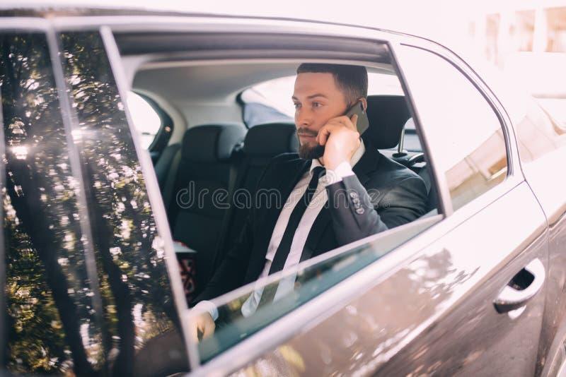 Молодой бизнесмен говоря на мобильном телефоне и смотря отсутствующий пока сидящ на заднем сиденье автомобиля стоковое изображение rf
