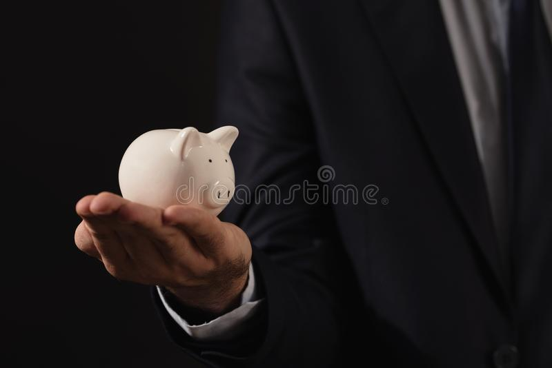 Молодой бизнесмен держа белую копилку финансы яичка диетпитания принципиальной схемы предпосылки золотистые стоковое изображение rf