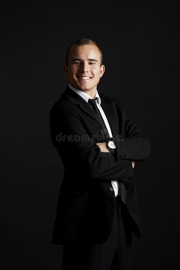 Молодой бизнесмен на черноте стоковая фотография