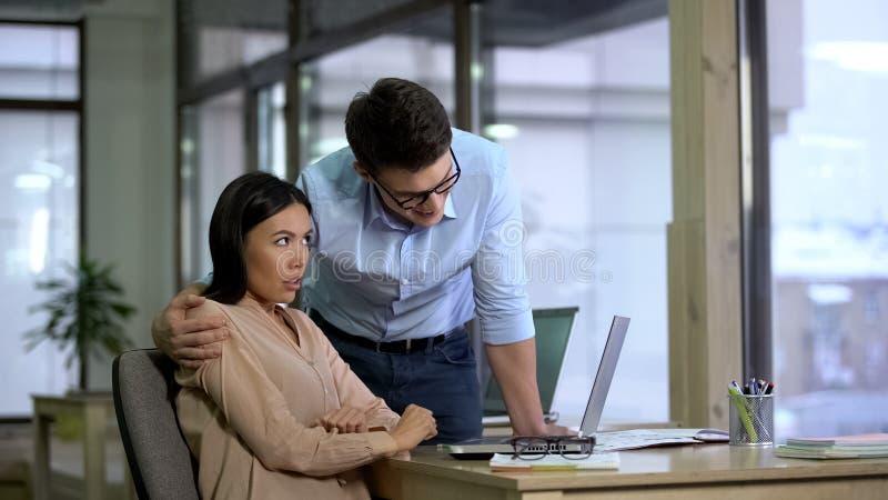 Молодой бизнесмен обнимая красивую женскую секретаршу, сексуальные домогательства, злоупотребление стоковое изображение rf