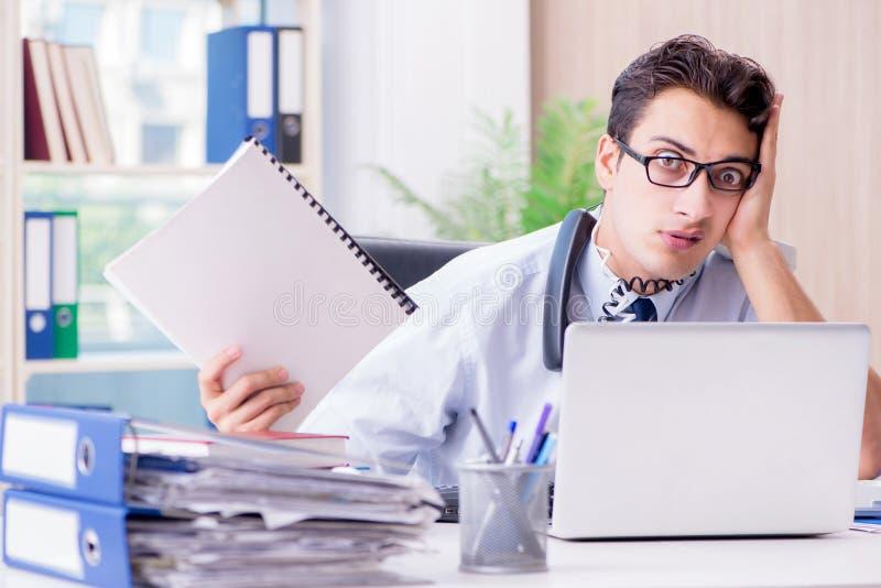 Молодой бизнесмен под давлением в офисе поставить задачи стоковая фотография