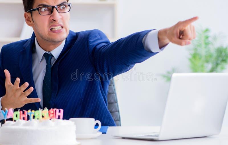 Молодой бизнесмен празднуя день рождения самостоятельно в офисе стоковое изображение