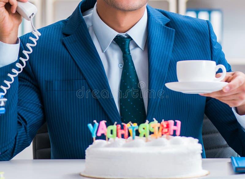 Молодой бизнесмен празднуя день рождения самостоятельно в офисе стоковые фото