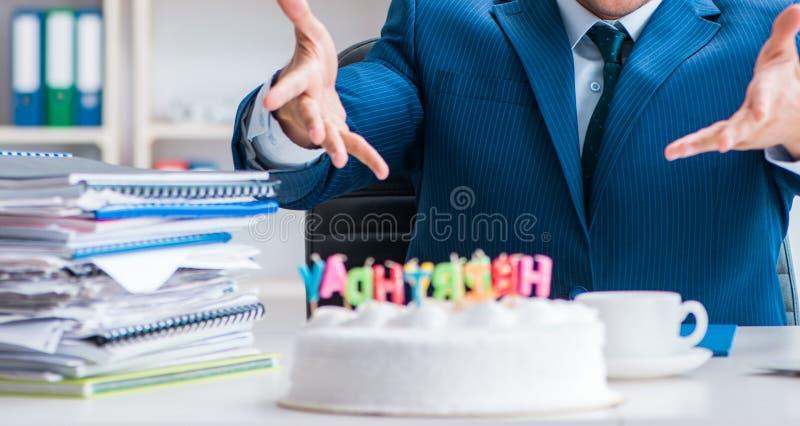 Молодой бизнесмен празднуя день рождения самостоятельно в офисе стоковое фото rf