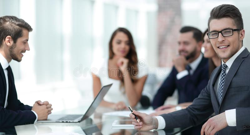 Молодой бизнесмен при его команда дела сидя на его столе стоковое изображение