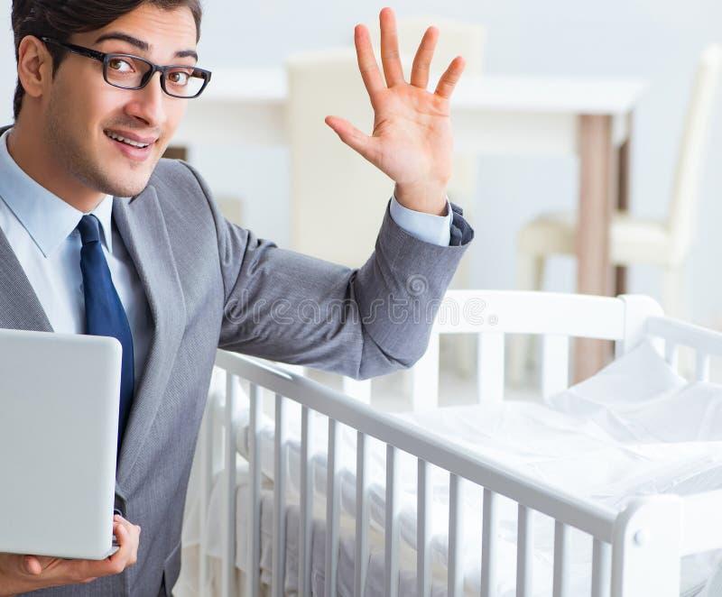 Молодой бизнесмен пробуя работать от заботить дома после newborn стоковые фото