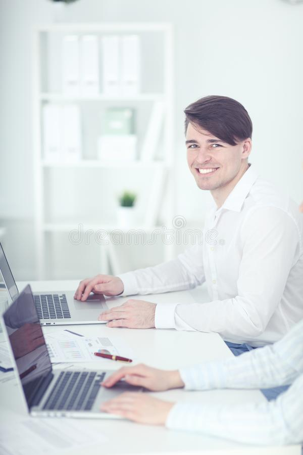 Молодой бизнесмен работая в офисе, сидящ на столе, смотря экран ноутбука стоковые изображения rf