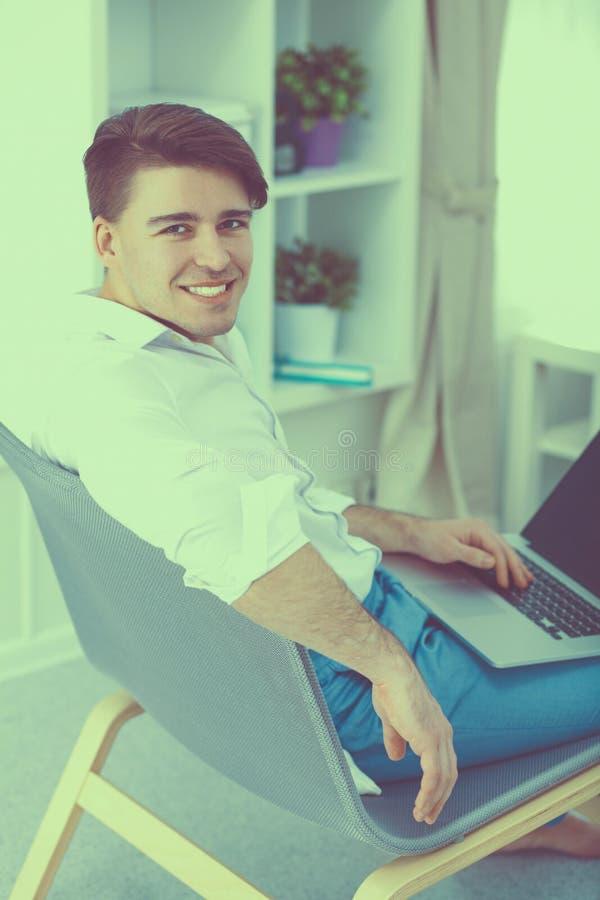 Молодой бизнесмен работая в офисе, сидя на столе стоковые изображения