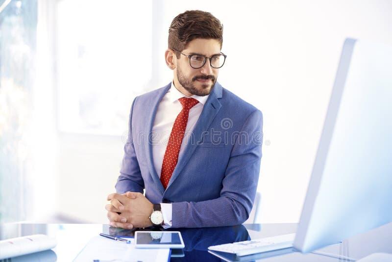 Молодой бизнесмен работая на его компьютере пока сидящ на offic стоковые изображения rf