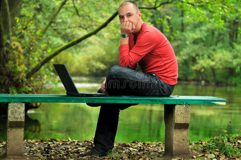 Молодой бизнесмен работая на компьтер-книжке напольной стоковые изображения